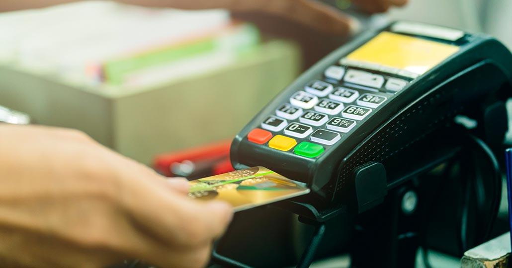 Hand schiebt Geldkarte in Lesegerät