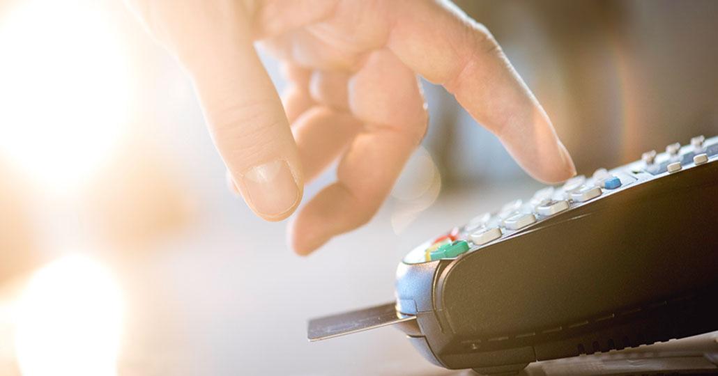 Hand tippt PIN in Kartenlesegerät