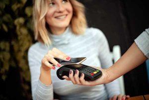 Frau hält Handy an Kartenlesegerät
